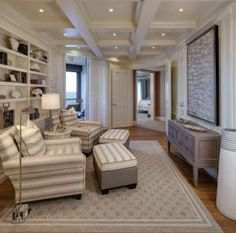 Elegant Florida Condo with Coastal Interiors   Library Bookshelves. Elegant library with coffered ceiling, paneled walls and built in bookshelves behind two custom hickory chair wide square arm chairs. #Library #Den #bookshelves #cofferedceiling #paneledwalls W Design Interiors
