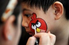 "A boy has a character from the popular computer game 'Angry Birds' painted on his face during the Philippine Animal Welfare Society's (PAWS) annual Halloween fund raising event entitled ""Scaredy Cats and Dogs: Year 8"" at the Eastwood Central Plaza in Manila on October 23, 2011. AFP photo"