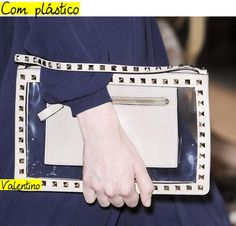 Além de aparecer em detalhes nos sapatos, o plástico também dá o ar da graça em bolsas e carteiras, como esta, de Valentino.