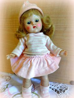 Adorable blonde strung Ginny wearing a 1951 Sister outfit. Outfit is tagged. Doll is in very good condition with thick eyebrows and lovely pink cheek coloring. Eye makeup has oxidized. Outfit has a little age fading but is generally very nice and clean and is tagged Vogue. Her eyelids show because her eyes do not open all the way, even when they are pushed up from inside. On her body are a few very small marks, perhaps from other outfits, one on her hip and a dot on her back and a couple of…