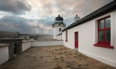 Clare Island Lighthouse is located off Ireland's western Atlantic coast. This luxury Lighthouse hotel offers a unique experience to its guests with breathtaking sea views of the Wild Atlantic Coast Lighthouse Hotel, Clare Island, Emerald Isle, Blue Books, Lighthouses, Shades Of Green, Hotel Offers, Ireland, Irish