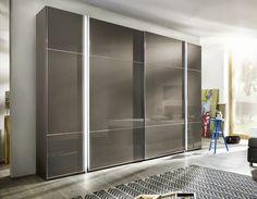 Linnenkast Marcato 3, combinatie van draaideuren aan de buitenzijde en schuifdeuren in het midden, gescheiden door een lichtlijst. Hier afgebeeld in de rompkleur bruin velours, met Sahara glas op de deuren.