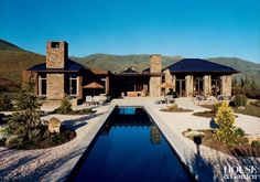 A dark blue pool complimentsthis Idaho house with detailing in Montana moss ledge stone.