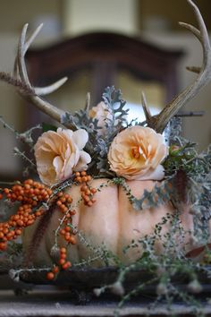 A pumpkin centerpiece with faux antlers. via Top 7 Ways to Decorate with Antlers