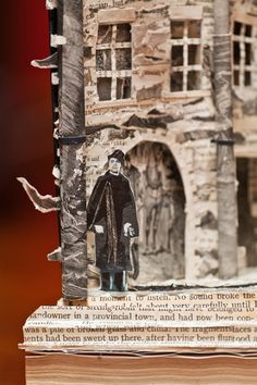 """Another sculpture from the """"Library Phantom"""": ...over at the Writer's Museum — it's not clear how long it had been there — was a sculpture propped atop the donations box in the Robert Louis Stevenson room. It was a street scene, with birds, people, cobblestones, all under a dangling moon hanging in the sky."""
