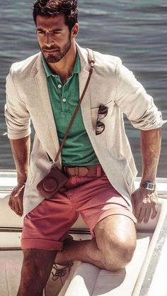 Try pairing a beige wool blazer with dusty pink shorts for a dapper casual get-up. For footwear go down the casual route with beige leather boat shoes.   Shop this look on Lookastic: https://lookastic.com/men/looks/blazer-polo-shorts-boat-shoes-belt-sunglasses-watch/11796   — Green Polo  — Beige Wool Blazer  — Dark Brown Sunglasses  — Brown Leather Belt  — Brown Leather Watch  — Pink Shorts  — Beige Leather Boat Shoes