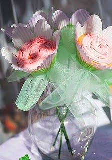 "Cupcake flowers! Flower liners are from Wilton.  Photos don't show it too well, but there is a little purple edible glitter on each flower.  ""Stems"" are bamboo skewers taped with floral tape, and held in place with green tulle bows."