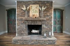 Living Room, Detail, AFTER The fireplace is flanked by twin arched wood doors, painted blue-green and distressed. The fireplace is resurfaced in dry stack stone, replacing a standard brick hearth and surround. Fixer Upper Hgtv, Magnolia Fixer Upper, Magnolia Homes, Magnolia Farms, Magnolia Market, Fireplace Design, Fireplace Mantels, Fireplace Ideas, Mantel Shelf