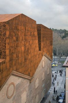Cor-ten steel facade on the addition built on top of, under and inside the existing stone building envelope. Caixa Forum by Herzog & de Meuron.