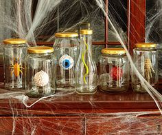 For Halloween party: suspend fake body parts and plastic creepy crawlers from lids of recycled jars with fishing line and hot glue