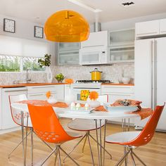 A Mod Eat-In  Space-extending moves and budget-stretching materials turn a tiny 1960s kitchen into a vibrant family hub. Orange countertops and accents pop against clean white cabinetry in this cheerful kitchen.