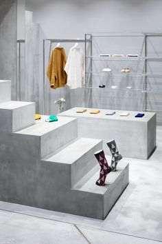 Clothing items hang from industrial piping. Contemporary Japanese footwear brand Marcomonde just landed its first retail space in fashion-forward Shibuya's PARCO luxury department store. Working with just under 215 square feet on the fourth floor of the building, Canadian architecture and design firm UUfie conceived the space to be centered around a free-standing, abstract, geometric sculpture. #InteriorDesign #RetailSpaces #Japan