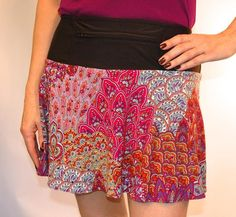 """PeacockOrchid SwingStyle This lightweight skirt has shades of pink, lavender, magenta, a hint of orange and purple sequins. Black wicking anti-ride undershorts hold two 4X5"""" pockets and the reverse flat-feld seams help resist chafing! The 12"""" zippered pocket in the waistband can be worn front or back."""