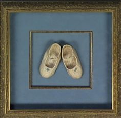 These delicate hand crocheted baby booties are artfully displayed on a blue suede double mat accented by a silver carved custom fillet and frame.
