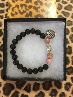 Yoga Mala Spiritual Bracelet made with 8 mm Lava Rock and Rhodochrosite beads.. A Buddha bead for the center piece and Tibetan Silver OHM Charm . This bracelet fit 6 3/4 to 7 1/4 inches but can be mad