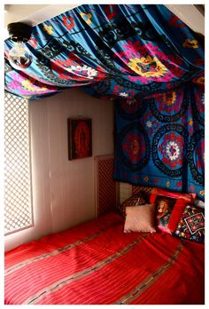 DIY tapestry headboard, could be cool with Christmas lights attached to wall and ceiling behind the fabric as a dim light option. Fabric can cover the outlet and cord.