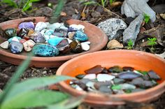 """Terra cotta dishes and colorful rocks and stones - beautiful """"treasures"""" in an outdoor setting."""