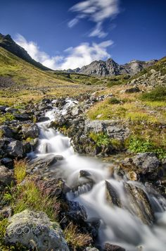 Water Stream - Stelvio National Park - A small water stream formed by the melting of glaciers in the Stelvio National Park. In the distance you can see the summit of Pizzo Paradisino 3305m, one of the mountains of the group Alps of Livigno.