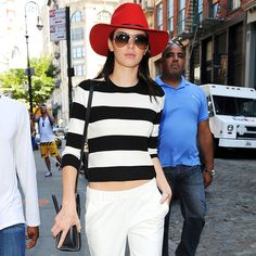 Red statement hat paired with simple separates for glam daywear.
