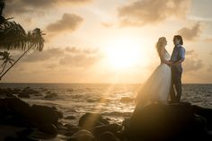 happy couple - bride and groom on dramatic rocks overlooking the beach and ocean at sunset - Destination wedding on Little Corn Island, an incredible tiny Caribbean island off the coast of Nicaragua - at Yemaya Island Hideaway Resort & Spa