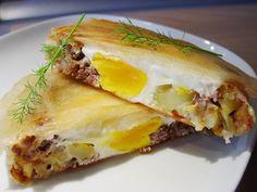 Bricks à la viande et à l'oeuf Ingrédients pour 6 bricks: - 6 feuilles de brick - 250 g de boeuf haché - 100 g d'emmental coupe en petits des - 2 pommes de terre moyennes - 2 gousses d'ail - 1 oignon - 6 oeufs - 1 bonne pincée d'origan et de basilic  - Sel, poivre - Huile de cuisson