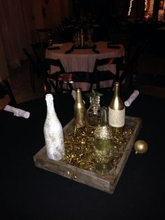 Gold and white bottles in a rustic wooden box.