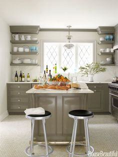 Designer Kelie Grosso opted for open shelving in this kitchen, which allows for fast and easy decor changes. Blue accents stand out against a neutral palette and makes us wonder just how dramatic (and stunning) more even brightly-colored dinnerware would look.