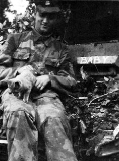 A youthful soldier of 12th-SS Hitlerjugend plays with a kitten on the glacias plate of his Panzer MKIV. He is wearing the distinctive Italian camouflage material popular to the unit in Normandy. His Iron Cross First Class is pinned to his pocket.