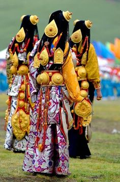 Some of Litang's most opulent ceremonial costumes.     Metal - i.e. silver or gold - is very important in Litang ceremonial costumes - Litang women wear the 'headphones'-like ornaments, which don't fall off as they are attached to a strap that goes across the head. Some women wear up to 30 extremely ornate plate sized ornaments all over their bodies - see other photos on this board for different views. // Litang Horse festival circa 2007