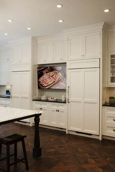 Stunning kitchen with custom white cabinetry accented with mixed polished nickel hardware alongside black counters with a subway tile backsplash.