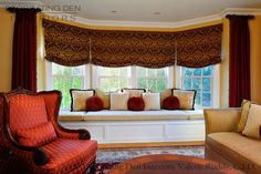 Red silk stationary side panels, red and gold damask roman shades, with custom bay window cushion and pillows, warm up this Traditional /Elegant Family Room.