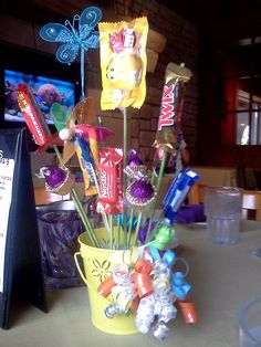 Candy flower centerpiece with mini pinwheel, butterfly, and curly ribbon bow accents.
