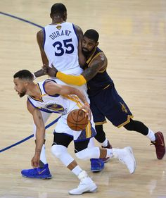 Kevin Durant of the Golden State Warriors sets a pick on Kyrie Irving of the Cleveland Cavaliers as teammate Stephen Curry drives to the basket...