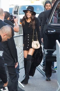 Sara Sampaio wears a sweater, button-front skirt, Chloé bag, fedora, fur coat, and thigh-high boots