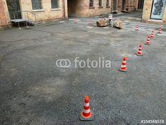 Mit Lübecker Hütchen abgesperrter Parkplatz auf altem Schotter in der Heyne Fabrik in Offenbach am Main