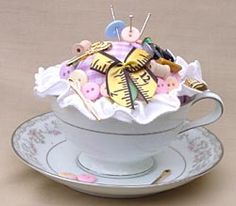Teacup & Saucer Pincushion    Teacup Pincushion    What You'll Need:  From Buttons Galore:      Dress It Up button packs:      (1) #348 A Stitch in Time      (1) #596 Sewing Room      (2) #43 Color Me Pastels        E6000 Craft Glue      Buttons Galore diagonal cutters    Other Items:      Teacup & Saucer      3 inch Styrofoam ball      1/4 yard lilac & white cotton gingham fabric      1 yard of 1' satin wired ribbon      (20) 3' long steel pins    Directions:  Cover foam ball with fabric…