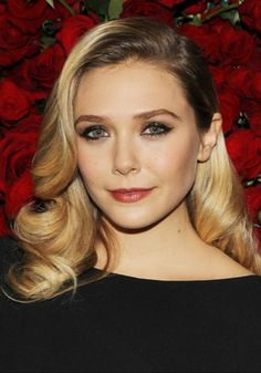 Elizabeth Olsen goes for a Veronica Lake style look with her tumbling waves and deep side parting.