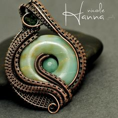 A lovely amazonite donut is the center of this mesmerizing wire wrapped pendant. Yards of copper wire are meticulously woven and wrapped, entirely by hand, then layered in enticing waves and curls to cup the stone in a fluid movement of wire. A small emerald Swarovski crystal accents the bail, an...
