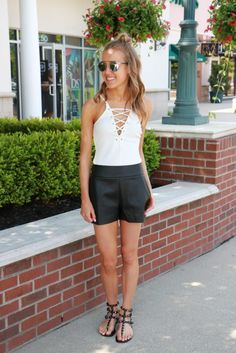 Hot Summer look for the girl on a budget! Express Lace-Up Bodysuit // Faux Leather Shorts // Valention Studded Sandals // Dior So Real Sunglasses // snapped by gracie
