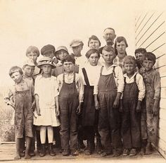 +~+~ Antique Photograph ~+~+  Class photograph from a long time ago.  There's quite a difference between how the children are dressed.  The girls seem to be in finer clothes but some of the boys have no shoes and are wearing tattered or soiled overalls.