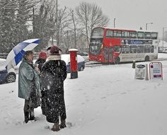 Outside the paper shop -   Biting cold and falling snow didn't deter these ladies from a good natter after buying their newspapers. A bus slithers it's way towards Birmingham on the 5 route from Solihull. 18/01/2013 by geoff7918