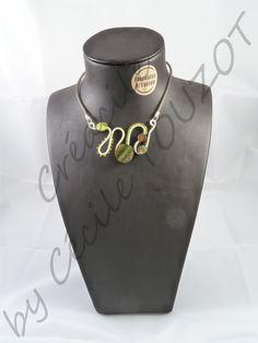 Pendentif en fil aluminium vert kaki et marron sur tour de cou en caoutchouc assorti.   Composé de perles de rocailles, d'un bouton fantaisie et de petits palets en nacre.   Ce bijou unique aux couleurs soft offre une fantaisie aux personnes soucieuses de discrétion.   Il s'accordera facilement à tout types de décolletés et à beaucoup de genres vestimentaires.
