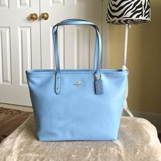 """Authentic Coach Crossgrain City Zip Tote Bag Authentic Coach Crossgrain City Zip Tote Bag. Made of crossgrain leather. Style F36875. Color- BlueJay with light gold hardware. New with tag. Dimensions- 12"""" L (bottom) or 16"""" L (top) x 10.25"""" H x 5.5"""" W & 9.5"""" handle drop height for shoulder wear. It has multiple inside pockets including a zip pocket and slide pockets. It is a top zip closure bag with fabric inside lining. No dust bag included. Coach Bags Totes"""
