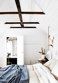 Ultra crisp bedroom with exposed wooden beams, and denim sheets
