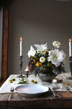 A timeless table setting with candles, fresh flowers and kumquats is at once elegant and rustic.