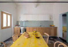 La cucina all'interno delG-Roc apartment a Barcellona, con piastrelle riutilizzate provenienti da altri progetti realizzati in precedenza. Il tavolo da pranzo è stato realizzato con lo stesso legno che percorre tutta la casa, verniciato a resina