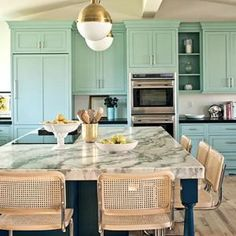 An eclectic yet classy mix: turquoise cabinets, vintage light fixtures, marble island, casual woven stools.