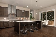 This sleek kitchen opens to indoor and outdoor dining space. The Hidden Pines 3402 plan, a new home built by Summit Homes at Hidden Pines. Issaquah, WA.