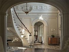 Georgian Colonial hall way with epic stair case and white wainscot panelling