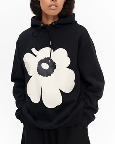 The Runoja hoodie is made of a thick cotton jersey blend and it features the large poppy flower of the Unikko (poppy) pattern on the front. The sweatshirt has drawstrings to tighten the hood and it is of unisex design and sizing.Marimekko's Poppy Pattern, African Textiles, Mini S, Off White Color, Marimekko, Long Toes, Hoodies, Sweatshirts, Black Hoodie
